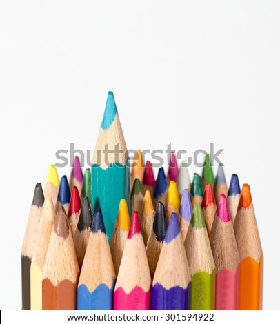 A set of colorful pencils on a white background. One pencil is getting a headstart. - stock photo