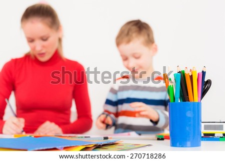 A set of coloring pencils with mother and son drawing in the background - stock photo
