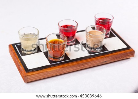 a set of cups with colored liqueurs - stock photo