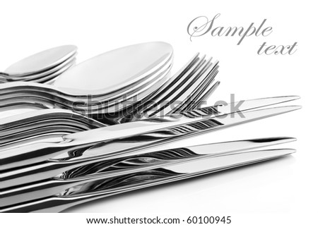 a Set of cutlery with stacked knifes, forks, spoons and tea spoons on a white background with space for text