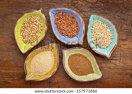 a set of five gluten free grains (sorghum, teff, amaranth,brown rice and buckwheat) - top view of leaf shape bowl against weathered, rustic wood - stock photo
