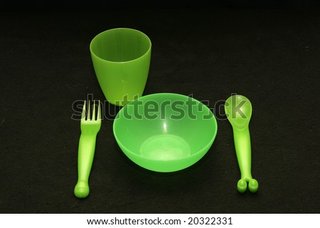 A set of green plastic tableware for kids - stock photo