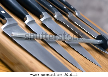 A set of high quality kitchen knives on a cutting board - stock photo