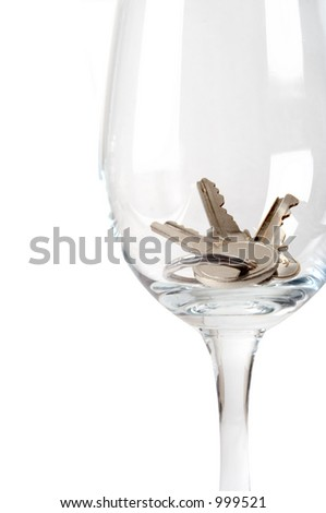 A set of keys in a wine glass symbolizing drinking and driving. - stock photo