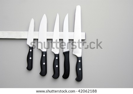 A set of knifes are hanging on a kitchen wall. - stock photo