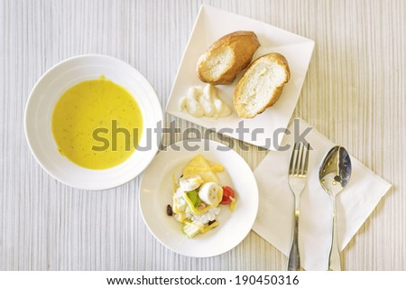 A set of meal including bread with cream, salad and pumpkin soup.