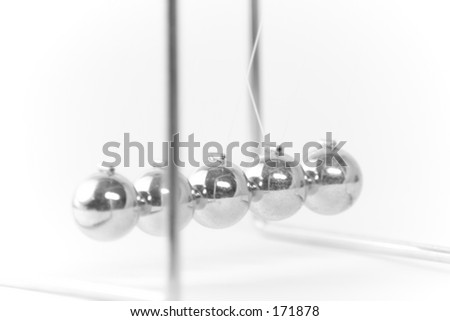 A set of metal balls suspended from strings.  Demonstrates Newton's laws of physics. - stock photo