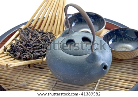A set of oriental teapot, cups and dry oolong tea on a wooden tray - stock photo