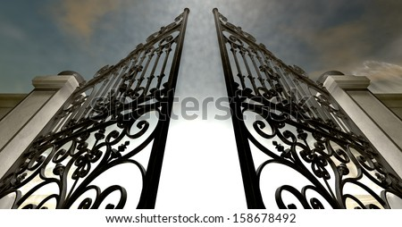 A set of ornate gates to heaven opening under an ethereal light and cloudy afterlife - stock photo