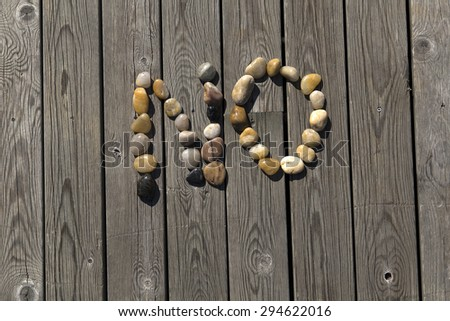 A set of pebbles on a wooden pier forming the word no