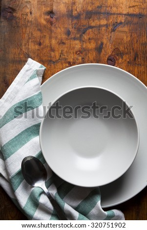 A set of plates on a wooden table. table setting - stock photo