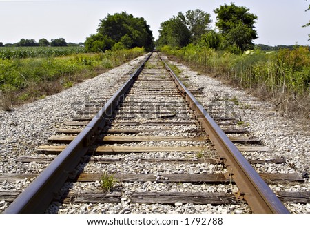 A set of railroad tracks coverge in the distant countryside