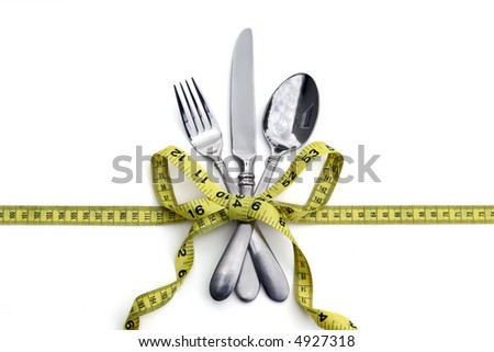 A set of silverware tied with a measuring tape in a bow. White background. Good for healthy eating or dieting concept. - stock photo