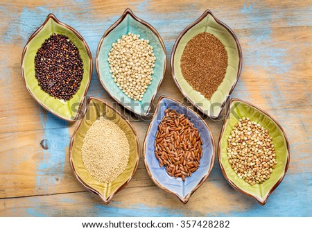 a set of six gluten free grains (black quinoa, sorghum, teff, amaranth,brown rice and buckwheat) - top view of leaf shape bowl against painted wood - stock photo