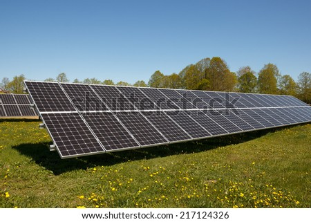 A set of solar panels on a field of grass - stock photo