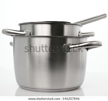 A set of stainless steel kitchenware on plain background with a natural reflection under it.