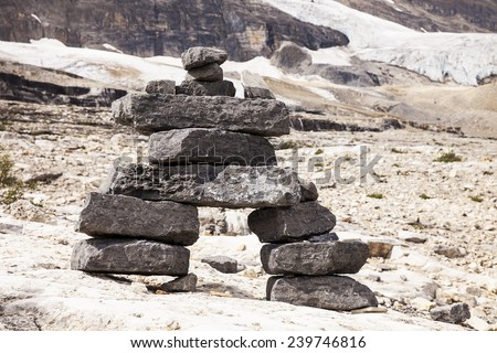 A set of stones are stacked on top of each other to form a figure of a person as a cairn, or marker, on the Iceline Trail. The background shows the Emerald Glacier in Yoho National Park in Canada - stock photo