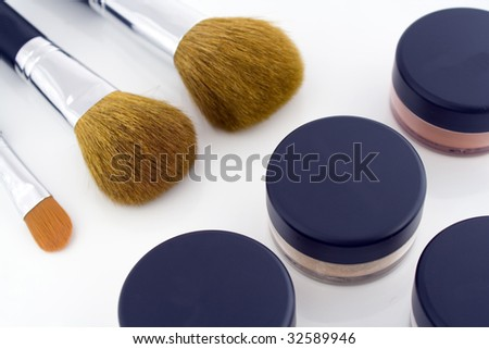 A set of three make-up brushes and four jars with mineral powder foundation. - stock photo