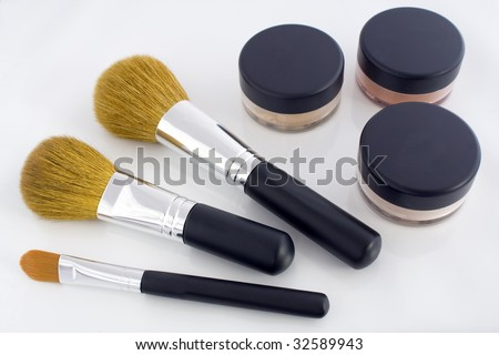 A set of three make-up brushes and three jars with mineral powder foundation. - stock photo