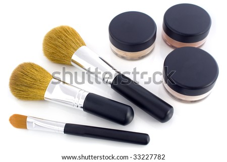 A set of three make-up brushes and three jars with mineral powder foundation. Isolated on white background.