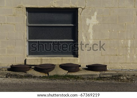 A set of utility covers in broken cement sidewalk. - stock photo