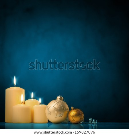 A set of white candles and Christmas ornaments in front of a blue background. - stock photo
