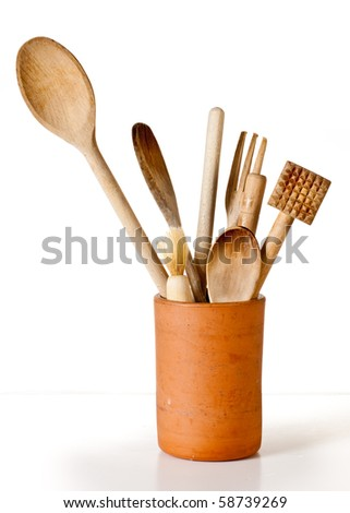 A set of wooden cooking utensils in a terracotta container against a white background