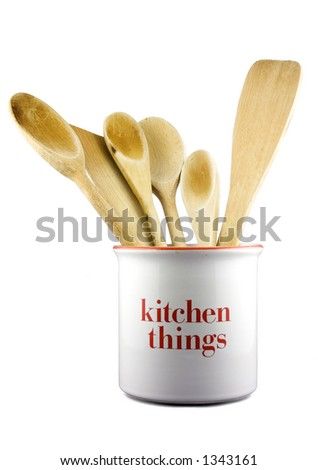 A set of wooden kitchen utensils in a ceramic pot. Isolated on white with path.