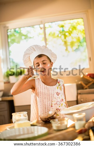 A seven years old girl with chef hat is standing at the kitchen table full of ingredients, licking melted chocolate on a wooden spoon. She has her eyes closed to better enjoy the taste - stock photo