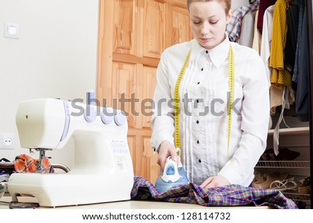 A sewer ironing a garment.