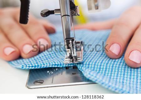 A sewer making a stitch on the fabric - stock photo