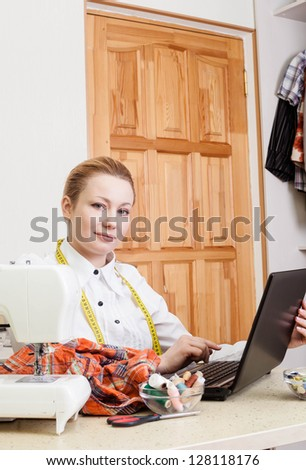 A sewer working on a laptop computer. - stock photo