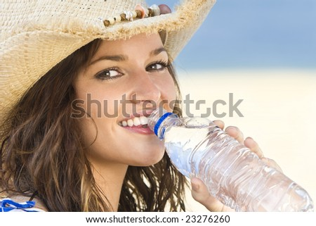 A sexy and beautiful young brunette woman sitting at the beach drinking a bottle of water with golden sand and the sea behind her - stock photo