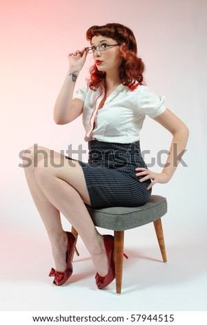 A sexy librarian pin-up girl on a soft pink background. - stock photo