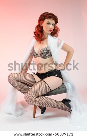 A sexy pin up girl draped in gauzy material. - stock photo