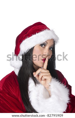 A sexy Santa Clause Asian woman in Christmas attire warning to be quiet and keep a secret during the holidays. - stock photo