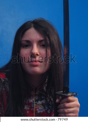 A sexy woman with a katana stares at the camera