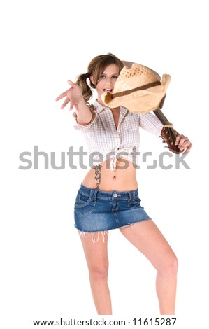 A sexy young barefooted cowgirl with pigtails smiling with a guitar over her shoulder and throwing her hat to the crowd - stock photo