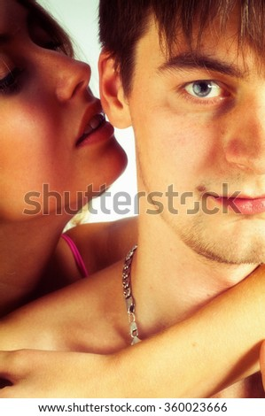 A sexy young topless couple embracing. beautiful young blond woman hugging Man. Young and fit caucasian adult couple in an embrace. Semi-nude and topless against a white background  - stock photo