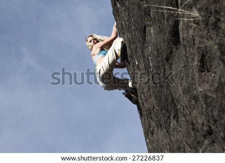 A sexy young woman climbing a stone wall
