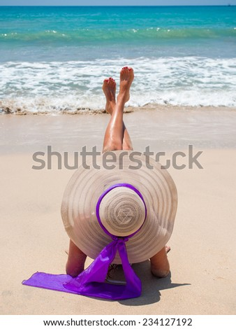 A sexy young woman or girl wearing a bikini and sun hat sitting on a deserted tropical beach in Bali - stock photo