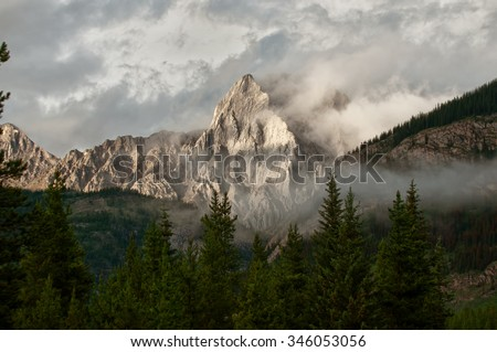 A shaded mountain in the distance with foreground trees and fog in the Rocky Mountains of Alberta. - stock photo