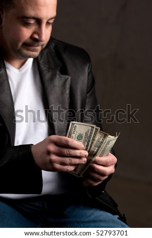 A shady looking man counting a handful of one hundred dollar bills. Shallow depth of field with focus on the money.