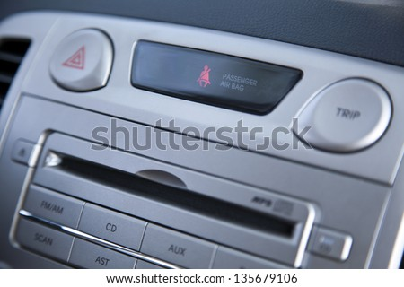 A shallow depth of field close up macro shot of part of the control panel of a car. Parts shown are the CD player and lit diagram indicating someone hasn't fasten his seat belt. - stock photo