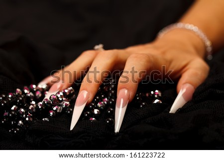 A sharp nailed woman's hand with pearls isolated on black  - stock photo