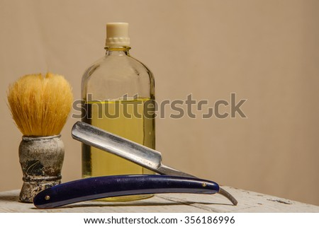 A sharp straight razor, brush and cologne aftershave - stock photo