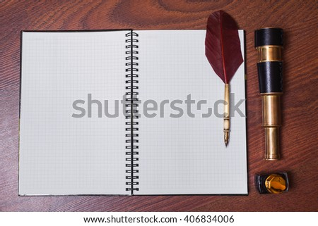 a sheet of paper from a notebook, fountain pen and ink, spyglass on wooden background, copyspace, open notebook with white sheets in a cage lying on the wooden background  - stock photo