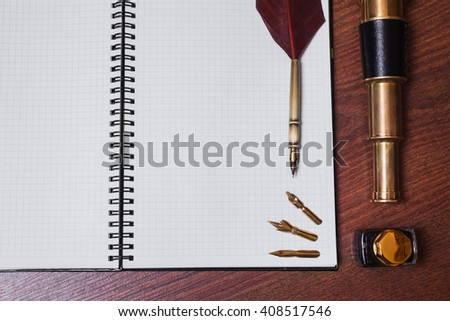 a sheet of paper from a notebook, fountain pen and ink, spyglass on wooden background, copyspace, white sheet of paper in the cage, fountain pen with metal tips, articles for writing, open notebook  - stock photo