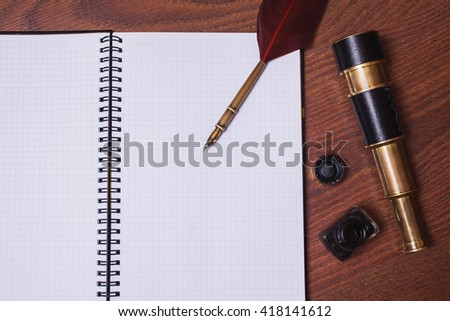 a sheet of paper from a notebook, fountain pen and ink, spyglass on wooden background, copyspace, open notebook for writing with a pen  - stock photo