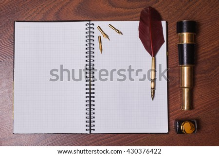 a sheet of paper from a notebook, fountain pen and ink, spyglass on wooden background, copyspace - stock photo